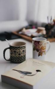 Kubki z kawą i książka.